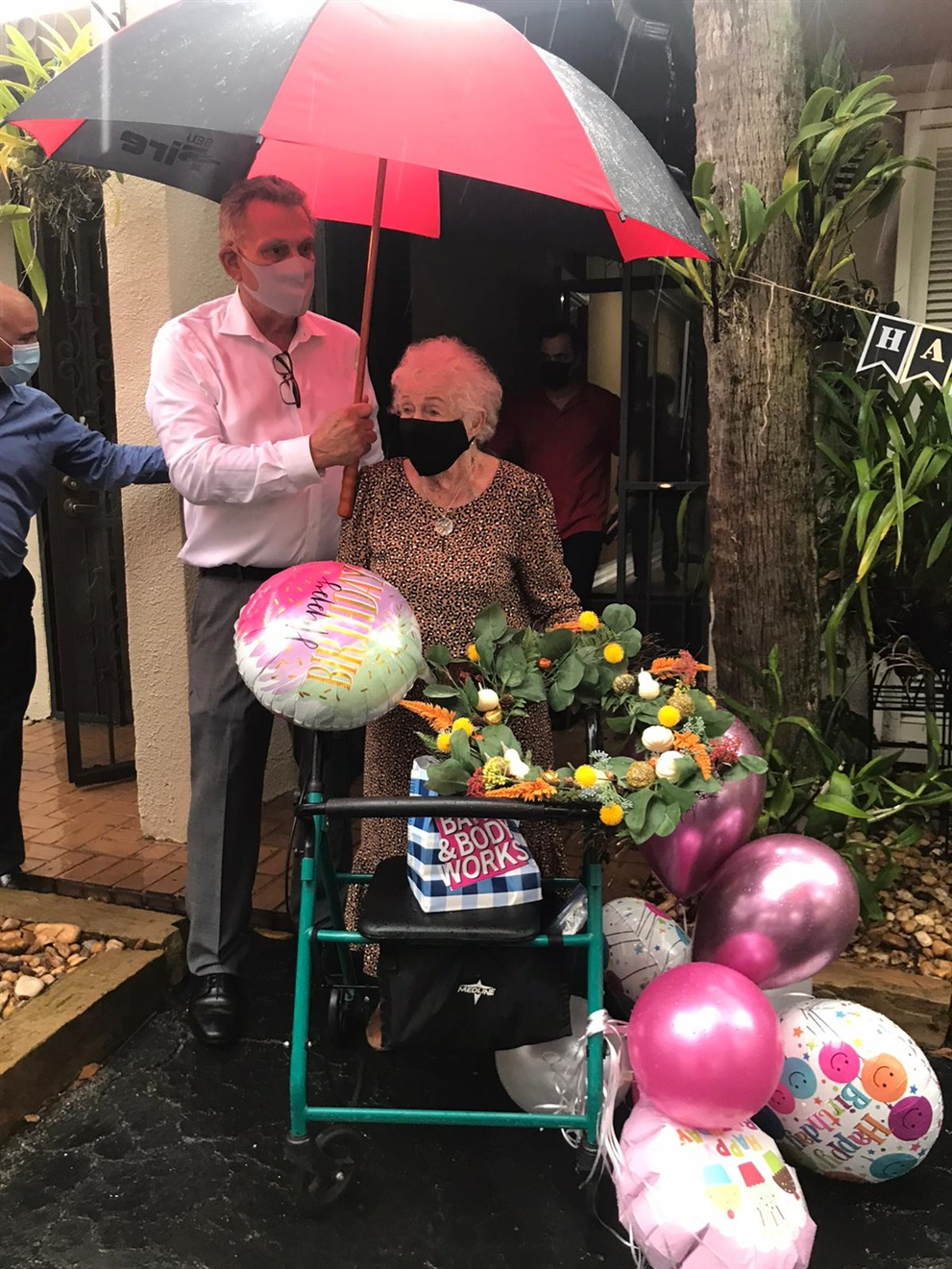Alex Ruiz of The Keyes Company holds an umbrella over Rosa Nell Hammer on Oct. 2 during her surprise 101st birthday party in Miami Lakes. Daniel Gandule is at left, and Allan Pelaez is in the background; they're both friends from the real estate indu