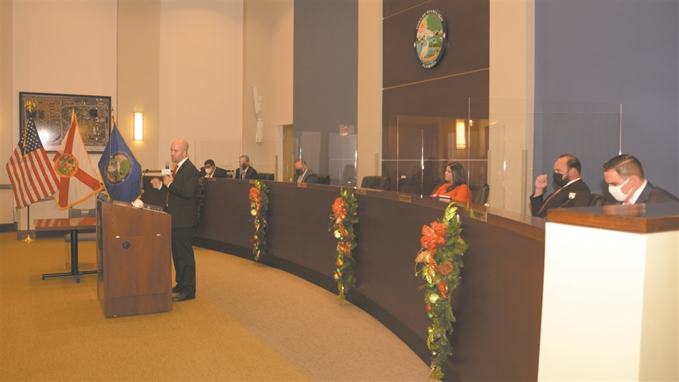 Miami Lakes Mayor Manny Cid shown at the podium above speaks at Town Hall during a Nov. 17 ceremony when Cid, Luis Collazo, Marilyn Ruano and Tony Fernandez were all sworn in for four year terms.  From left to right are Mayor Manny Cid; Councilman To